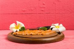 Salmon sushi on cutting board with flower on wood color pink.  royalty free stock image