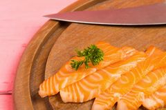 Salmon sushi on cutting board with flower on wood color pink clo. Seup stock photography