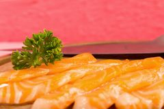 Salmon sushi on cutting board with flower on wood color pink clo. Seup royalty free stock photography