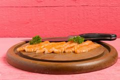 Salmon sushi on cutting board with flower on wood color pink.  royalty free stock images