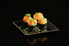 Salmon sushi foursome. On mirrored black background Stock Photos