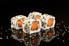 Salmon sushi foursome. Salmon sushi with sesame on mirrored black background Stock Image