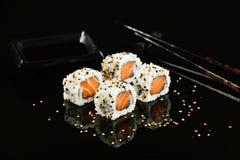 Salmon sushi foursome. Salmon sushi with sesame on mirrored black background Royalty Free Stock Photos