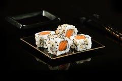 Salmon sushi foursome. Salmon sushi with sesame on mirrored black background Royalty Free Stock Photo