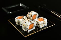 Salmon sushi foursome. Salmon sushi with sesame on mirrored black background Royalty Free Stock Photography