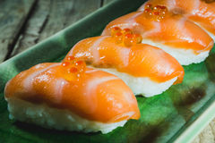 Salmon sushi. Salmon sushi with ikura on green plate Royalty Free Stock Image