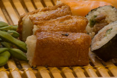 Salmon Sushi, Inari, Edamame Beans and Nori Rolls on a Bamboo Platter Royalty Free Stock Photography