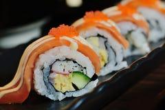Salmon sushi nigiri in chopsticks over black background Royalty Free Stock Photo