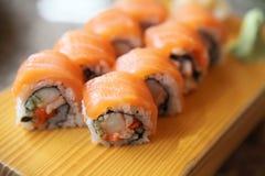 Salmon sushi rolls. On wooden plate stock photos