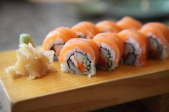 Salmon sushi rolls. On wooden plate stock photography