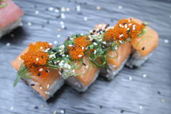 Salmon Sushi rolls on a ceramic plate. Salmon Sushi rolls with caviar and seaweeds on a ceramic plate Stock Photo