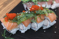 Salmon Sushi rolls on a ceramic plate. Salmon Sushi rolls with caviar and seaweeds on a ceramic plate Stock Photography