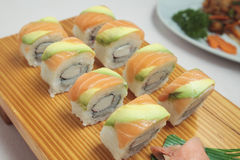 Salmon Sushi rolls. On a wooden plate Royalty Free Stock Images