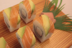 Salmon sushi rolls. On a wooden plate Stock Images