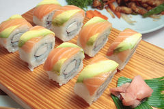 Salmon sushi rolls. On a wooden plate Stock Image