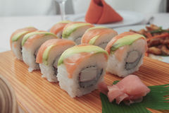 Salmon sushi rolls on a wooden plate. Salmon and avocado sushi rolls on a wooden plate Stock Photos