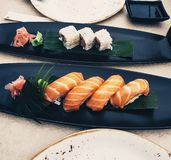 Salmon nigiri sushi, next to maki rolls on leaves in black plates - Japanese cuisine with soy sauce and wasabi - raw fish royalty free stock photos