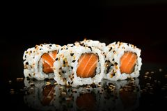Salmon sushi foursome. Salmon sushi with sesame on mirrored black background Royalty Free Stock Image