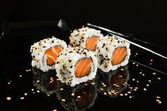 Salmon sushi foursome. Salmon sushi with sesame on mirrored black background Stock Photos