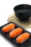 Salmon Sushi with soup. Salmon sushi served on black tray with soup in black bowl placed on bamboo base Stock Image