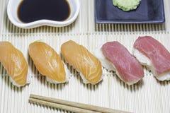 Salmon sushi and tuna sushi with wasabi and sauce. Salmon sushi and tuna sushi with wasabi and sauce on bamboo plate Stock Photo