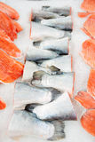 Salmon tails and fillet on cooled market display Royalty Free Stock Image