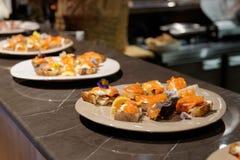 Salmon tapas on open kitchen counter, hard light stock photography