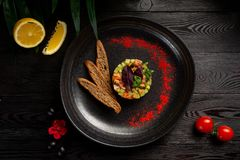 Salmon tar-tar with spices on a black plate stock photography
