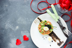 Salmon tartare with avocado black caviar and quail egg on Valentines Day , aphrodisiac food for lovers , festive delicacy. Appetizer , romantic seating place royalty free stock photos