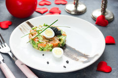 Salmon tartare with avocado black caviar and quail egg on Valentines Day , aphrodisiac food for lovers , festive delicacy. Appetizer , romantic seating place stock photo