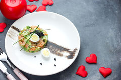 Salmon tartare with avocado black caviar and quail egg on Valentines Day , aphrodisiac food for lovers , festive delicacy. Appetizer , romantic seating place stock image