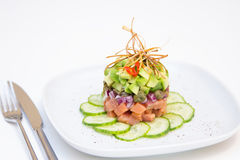 Salmon tartare with avocado, cucumber, capers and onions Royalty Free Stock Images