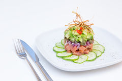 Salmon tartare with avocado, cucumber, capers and onions Royalty Free Stock Photos