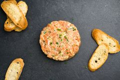 Salmon tartare top view. A dish made with chopped fresh raw salmon fish, avocado, tartar sauce and crackers or bread. This healthy dish is often served as Stock Photo