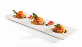 Salmon tartare on white table. Salmon tartar with red caviar and basil leaves on white square plate isolated on white background royalty free stock image