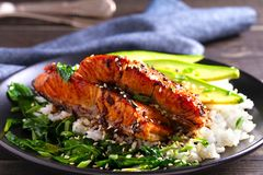 Salmon teriyaki rice bowl with spinach and avocado. Salmon teriyaki rice bowl with spinach and avocado stock image