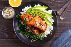 Salmon teriyaki rice bowl with spinach and avocado. stock photography