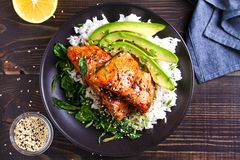 Salmon teriyaki rice bowl with spinach and avocado. View from above, top studio shot royalty free stock photography