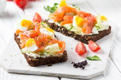Salmon toast with cream cheese, cucumber and egg. Delicious lunch, healthy food, fish sandwich, diet snack. Salmon toast with cream cheese, cucumber and egg royalty free stock photos