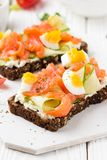 Salmon toast with cream cheese, cucumber and egg. Delicious lunch, healthy food, fish sandwich, diet snack. Salmon toast with cream cheese, cucumber and egg stock images