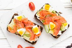 Salmon toast with cream cheese, cucumber and egg. Delicious lunch, healthy food, fish sandwich, diet snack. Salmon toast with cream cheese, cucumber egg royalty free stock images