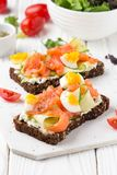Salmon toast with cream cheese, cucumber and egg. Delicious lunch, healthy food, fish sandwich, diet snack. Salmon toast with cream cheese, cucumber egg stock image