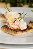 Salmon toasts. Salmon and creme fraiche toasts with chives to garnish Stock Photo