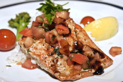 Salmon with Tomatoes and Basil Sauce. Salmon prepared with a tomato and basil sauce, served on a bed of rice on a plate decorated with lemons, broccoli,  and Royalty Free Stock Photography