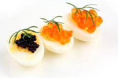 Salmon, trout and sturgeon caviar served on quail eggs Royalty Free Stock Photos