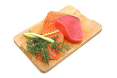 Salmon and tuna fish on white. Fresh raw salmon and tuna fish  pieces on wooden plate isolated on white background Royalty Free Stock Images