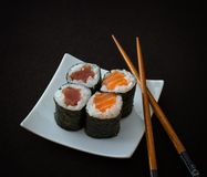 Salmon, tuna maki sushi and chopstick on black Royalty Free Stock Photography