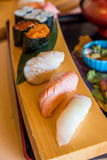 Salmon, tuna and scallop sushi on wooden plate Stock Photos