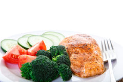 Salmon and Vegetable Dinner with Fork. A dinner of baked salmon, broccoli, tomatoes and cucumber Stock Photography