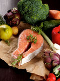 Salmon with Vegetables. Perfect Raw Steak of Salmon on Parchment Paper and Arrangement of Raw Vegetables with Broccoli, Artichokes,  Spring Onion, Tomatoes and Royalty Free Stock Photos
